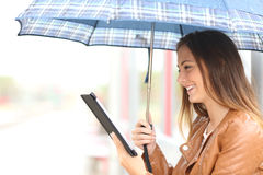 Woman reading ebook or tablet under the rain. Profile of a woman reading ebook or tablet under an umbrella in a rainy day in a generic place Royalty Free Stock Image