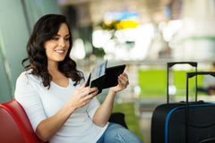 Woman reading email airport. Young woman reading her email on tablet computer while waiting for flight at airport Royalty Free Stock Images