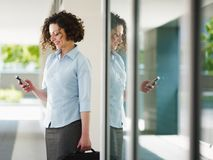 Woman reading emails outdoor. Woman standing out of office building and reading emails on mobile phone. Horizontal shape, Copy space royalty free stock image