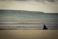 Woman reading on empty chilly beach. With moody cloud overhead. Mallorca, Balearic islands, Spain in November Royalty Free Stock Photo
