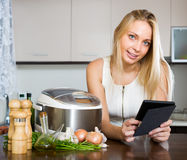 Woman reading ereader near multicooker Stock Images