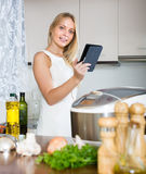 Woman reading ereader near multicooker Stock Photography