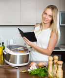 Woman reading ereader near multicooker Stock Image