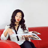 Woman reading fashion magazine at home Royalty Free Stock Images