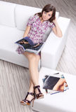 Woman  reading fashion  magazine on sofa Stock Photo