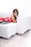 Woman  reading fashion  magazine on sofa Stock Photos
