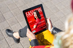 Woman reading fashion magazine on tablet royalty free stock photo