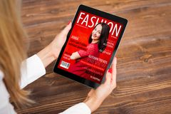 Woman reading fashion magazine on tablet stock images