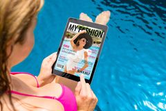 Woman reading fashion magazine on tablet. royalty free stock photos