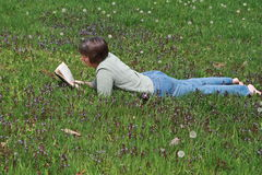 Woman reading in field. Middle-aged woman lying down in field reading novel royalty free stock photo