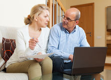 Woman reading finance documents with husband. In home interior Stock Images