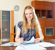 Woman reading financial document at home Royalty Free Stock Image