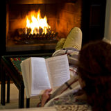 Woman reading by fireplace. Back view of a relaxing woman reading a book in front of a wood burning fireplace Royalty Free Stock Photography