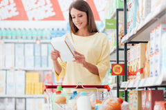 Woman reading food labels. Young woman doing grocery shopping at the supermarket and reading food labels with ingredients on a box, shopping and nutrition Stock Photography