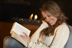 Woman reading in front of fire at home Stock Photo