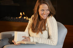 Woman reading in front of fire at home Stock Images