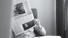 Woman reading German newspaper in armchair Stephen Hawking death stock video footage