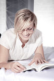 Woman reading with glasses Royalty Free Stock Photo
