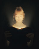 Woman reading a glowing Bible. stock photo