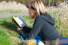 Woman Reading on Grass Royalty Free Stock Images
