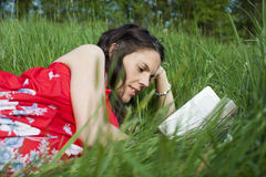 Woman Reading On Grass Stock Images
