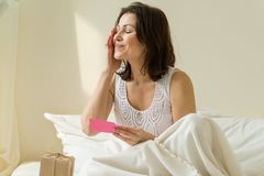 Woman is reading greeting card and looking at a surprise gift. Happy mature woman is reading greeting card and looking at a surprise gift, sitting in bed in the Royalty Free Stock Images