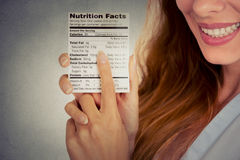 Woman reading healthy food nutrition facts. Closeup cropped portrait image woman reading healthy food nutrition facts isolated on gray wall background Stock Photo