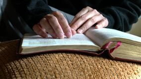 Woman reading her bible, closeup. Fingers going line by line of the text.