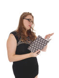 Woman reading in her journal. A lovely blond woman standing waist up in a black dress and glasses Stock Photo