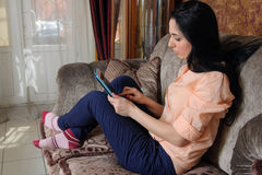 Woman reading her pad pensively. Royalty Free Stock Photo