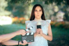 Shy Actress Auditioning for Movie Film Video Casting. Woman reading her part on a microphone for a role beying shy and having stage fright Royalty Free Stock Photos