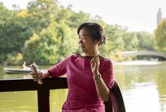 Woman reading on her phoen stock photography