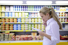 Woman reading her shopping list in the supermarket Stock Photo