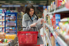 Woman Reading Her Shopping List In The Supermarket Royalty Free Stock Images