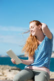 Woman reading her tablet in a sea breeze Stock Photo