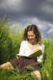Woman reading in high grass Stock Images