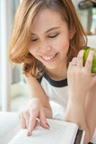 Woman reading and holding an apple Royalty Free Stock Photo