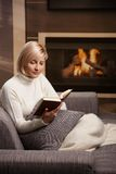 Woman reading at home. Woman sitting on sofa at home reading book, looking down Stock Photo