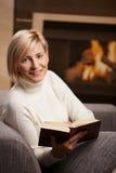 Woman reading at home. Woman sitting on sofa at home reading book, looking at camera, smiling Stock Image