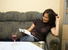Woman reading at home. A woman sitting in a sofa, relaxing with a magazine. A glass of red wine on the table Stock Photography