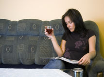 Woman reading at home. A woman sitting in a sofa, relaxing with a magazine. A glass of red wine in her hand Royalty Free Stock Images