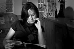 Woman reading at home. A woman sitting in an armchair, relaxing with a newspaper. Directional light. Monochrome picture Royalty Free Stock Images