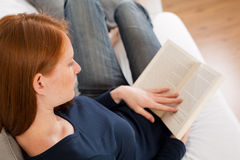 Woman Reading at Home. A young Caucasian woman reading a book at home Stock Image
