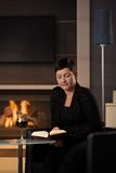 Woman reading at home. Young woman sitting in front of fireplace at home on a cold winter day, reading book Royalty Free Stock Photo