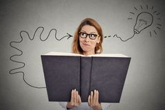 Woman reading a huge book has a good idea Royalty Free Stock Image