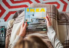 Woman reading IKEA catalog cover before furnishing house Stock Photos