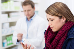 Woman reading information on a box of medication Royalty Free Stock Image