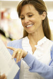 Woman Reading Ingredients On Packet In Supermarket Stock Image