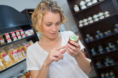 Woman reading ingredients product in shop. Woman reading ingredients of a product in shop Royalty Free Stock Photo