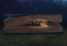 Woman reading inside a huge book. At night stock photo